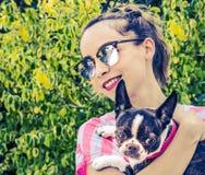 Mujer sonriente moderna joven con su perro en una actitud casual Imagenes de archivo