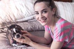Mujer sonriente moderna joven con su perro en una actitud casual Fotografía de archivo libre de regalías