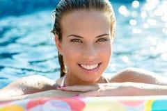 Mujer sonriente morena que se relaja en piscina foto de archivo