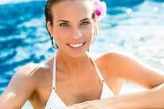 Mujer sonriente morena que se relaja en piscina fotos de archivo