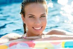 Mujer sonriente morena que se relaja en piscina Imágenes de archivo libres de regalías