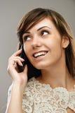 mujer sonriente Oscuro-cabelluda que habla en el teléfono Foto de archivo libre de regalías