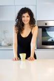 Mujer sonriente por la mañana en cocina fotografía de archivo libre de regalías