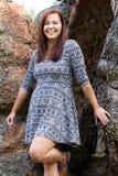 Mujer sonriente por las rocas foto de archivo