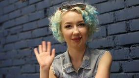 Mujer sonriente positiva amistosa que agita con su mano, amigos de granizada en la reunión almacen de metraje de vídeo