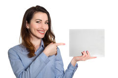Mujer sonriente positiva en camisa azul que señala en el pedazo en blanco de Fotos de archivo libres de regalías