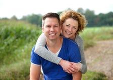 Mujer sonriente que abraza a su novio al aire libre Imagen de archivo
