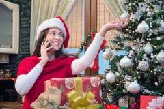 Mujer sonriente que adorna el árbol de navidad y que habla en el pH móvil Imagen de archivo