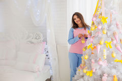 Mujer sonriente que adorna el árbol del Año Nuevo Fotografía de archivo