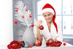 Mujer sonriente que adorna para la Navidad Imagenes de archivo