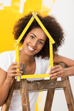 Mujer sonriente que adorna su nueva casa Imágenes de archivo libres de regalías