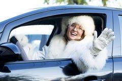 Mujer sonriente que agita de una ventanilla del coche Fotografía de archivo