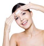 Mujer sonriente que aplica la crema cosmética en la frente Imagen de archivo