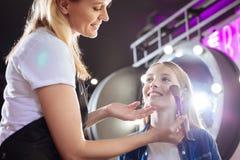 Mujer sonriente que aplica maquillaje a la cara de las muchachas Fotos de archivo