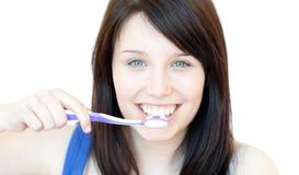 Mujer sonriente que aplica sus dientes con brocha Imagenes de archivo