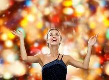 Mujer sonriente que aumenta las manos y que mira para arriba Foto de archivo
