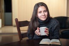 Mujer sonriente que bebe el té delicioso que se sienta en la tabla Fotografía de archivo libre de regalías