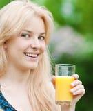 Mujer sonriente que bebe el zumo de naranja Imagen de archivo