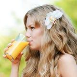 Mujer sonriente que bebe el zumo de naranja Imágenes de archivo libres de regalías