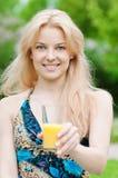 Mujer sonriente que bebe el zumo de naranja Imagen de archivo libre de regalías