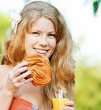 Mujer sonriente que bebe el zumo de naranja Imagenes de archivo