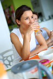 Mujer sonriente que bebe el zumo de naranja en cocina Fotografía de archivo