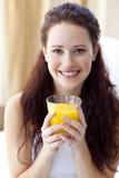 Mujer sonriente que bebe el zumo de naranja en dormitorio Fotografía de archivo
