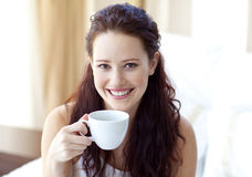 Mujer sonriente que bebe una taza de café en dormitorio Fotografía de archivo