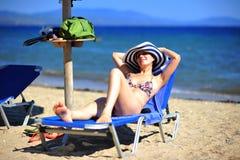 Mujer sonriente que broncea en sunbed en la playa Imagen de archivo