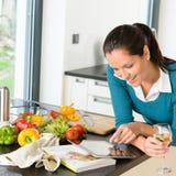 Mujer sonriente que busca verduras de la cocina de la tablilla de la receta Fotografía de archivo