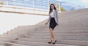 Mujer sonriente que camina abajo de escalera Fotografía de archivo libre de regalías