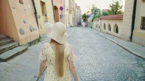 Mujer sonriente que camina en la calle Mujer bonita alegre en el sombrero blanco que mira detrás la cámara mientras que camina en almacen de video