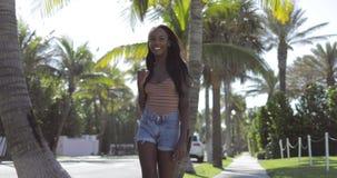 Mujer sonriente que camina en la calle soleada metrajes