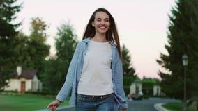 Mujer sonriente que camina en la calle y el encuentro de la ciudad del novio con las flores almacen de video