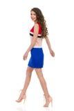 Mujer sonriente que camina en Mini Dress And High Heels foto de archivo