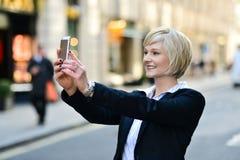 Mujer sonriente que captura un tiro del uno mismo Fotografía de archivo