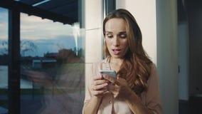 Mujer sonriente que charla en el teléfono móvil Retrato de la mujer feliz que envía el mensaje almacen de video