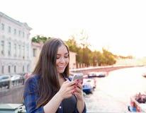 Mujer sonriente que charla en red social vía el teléfono móvil, colocándose al aire libre en la igualación cerca del río del terr Fotos de archivo libres de regalías