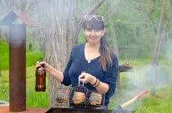 Mujer sonriente que cocina al aire libre sobre un Bbq Fotografía de archivo libre de regalías