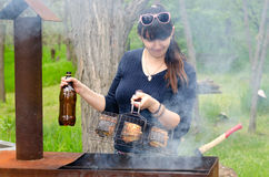 Mujer sonriente que cocina al aire libre sobre un Bbq Fotos de archivo