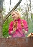 Mujer sonriente que cocina kebabs sobre un fuego del Bbq Imagenes de archivo