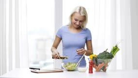 Mujer sonriente que cocina la ensalada vegetal en casa almacen de video