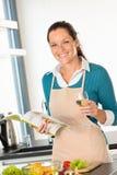 Mujer sonriente que cocina verduras de la receta de la cocina a casa Foto de archivo