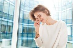 Mujer sonriente que coloca la ventana cercana en oficina y la risa Fotografía de archivo libre de regalías