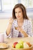 Mujer sonriente que come cereal Imágenes de archivo libres de regalías