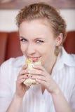 Mujer sonriente que come el abrigo fotografía de archivo libre de regalías