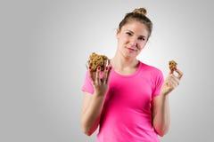 Mujer sonriente que come las galletas de harina de avena sanas Fotografía de archivo libre de regalías