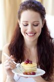 Mujer sonriente que come un postre dulce Fotos de archivo libres de regalías