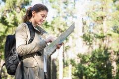 Mujer sonriente que comprueba el mapa Imagen de archivo