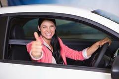 Mujer sonriente que conduce mientras que da los pulgares para arriba Imagenes de archivo